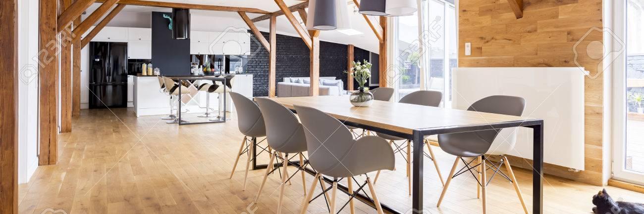 Diseño interior de madera del apartamento loft moderno espacio abierto con  mesa familiar, sillas, vigas, cocina, sala de estar y grandes ventanales ...