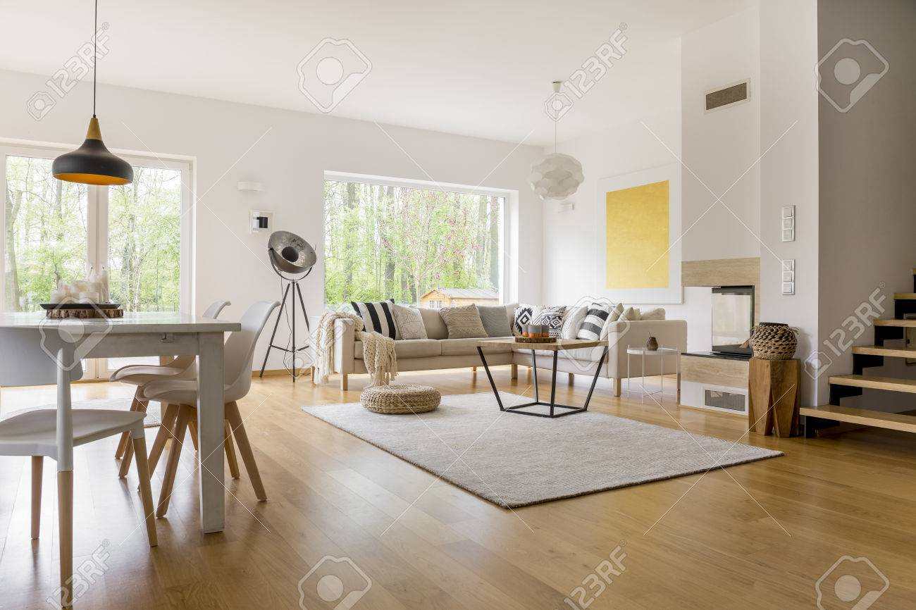 Beige Sofa With Pillows In Multifunctional Living Room With Dining Table  And White Chairs Stock Photo