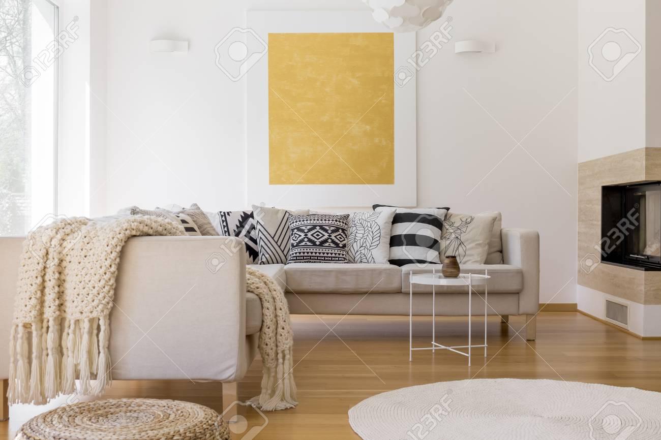Grande Peinture Dorée Sur Le Mur Blanc Dans Un Salon Unique Avec Cheminée Et Tapis Blanc