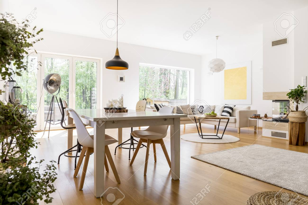 Plants Near Dining Table With White Chairs In Spacious Living ...