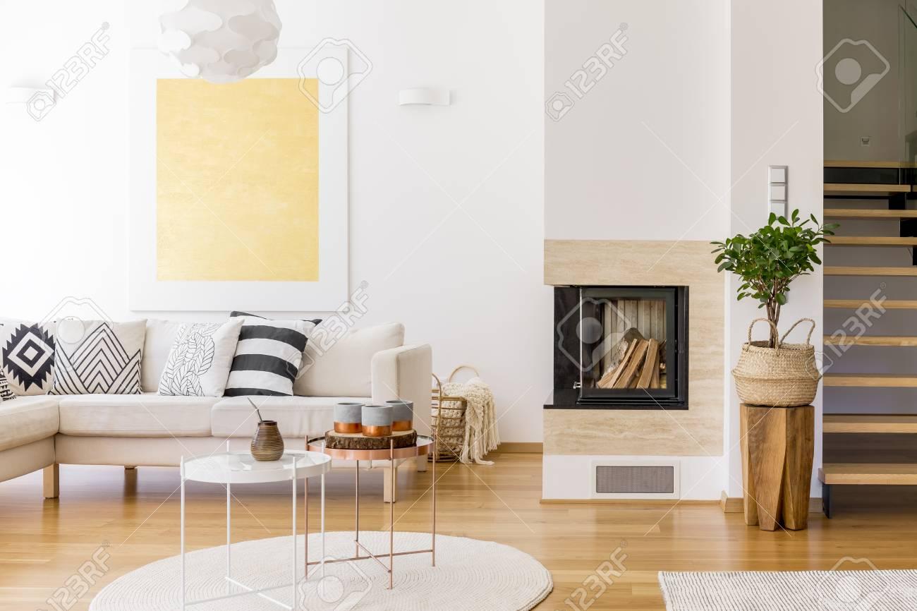 Table basse en cuivre sur un tapis blanc dans le salon avec cheminée et  peinture or sur le mur