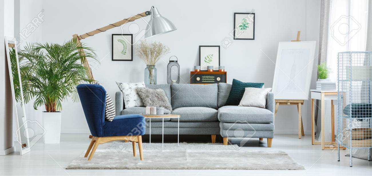 Stylish Living Room With Retro Velvet Chair And Easel Stock Photo