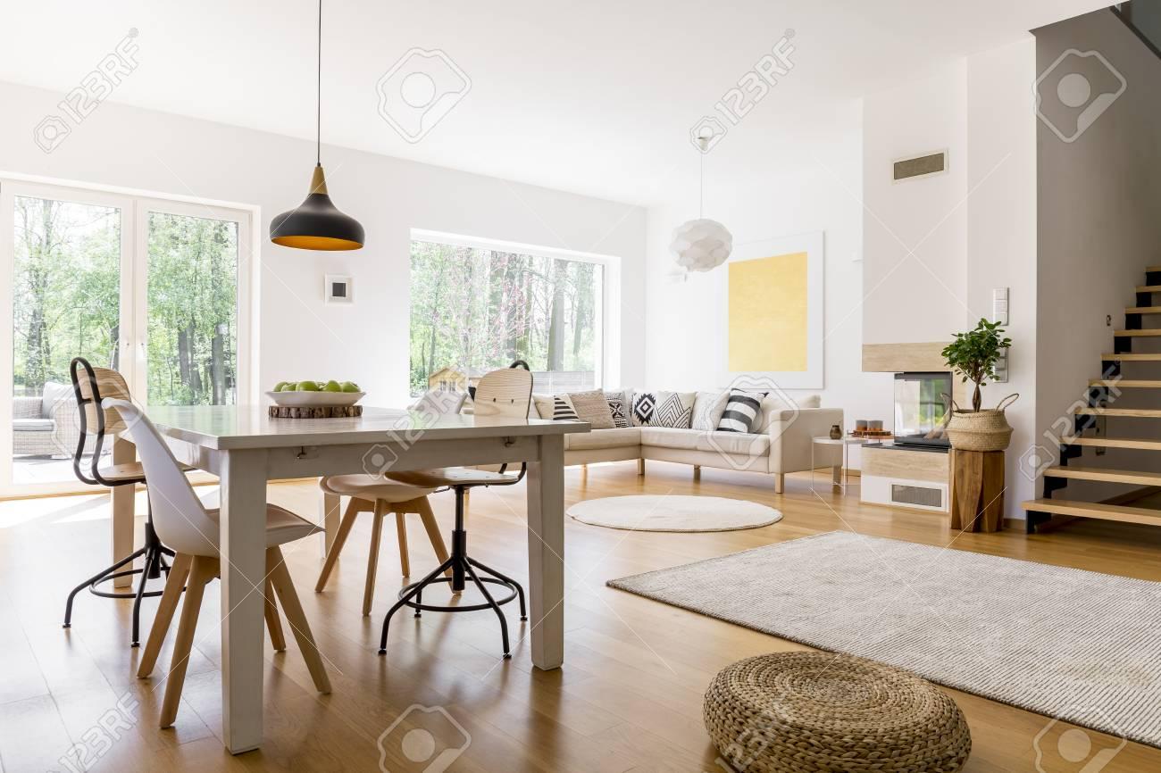 Lámpara de diseño negro encima de la mesa de comedor en la amplia sala de  estar con puf trenzado en el piso de madera