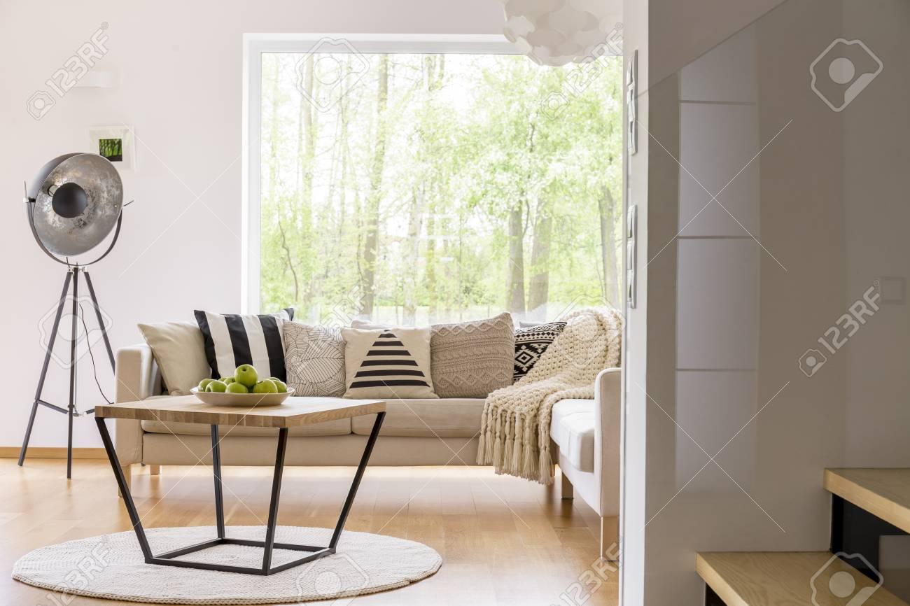 Gemusterte Kissen Auf Beige Sofa Und Entworfene Tabelle Mit Äpfeln Auf  Platte Im Modernen Wohnzimmer Standard
