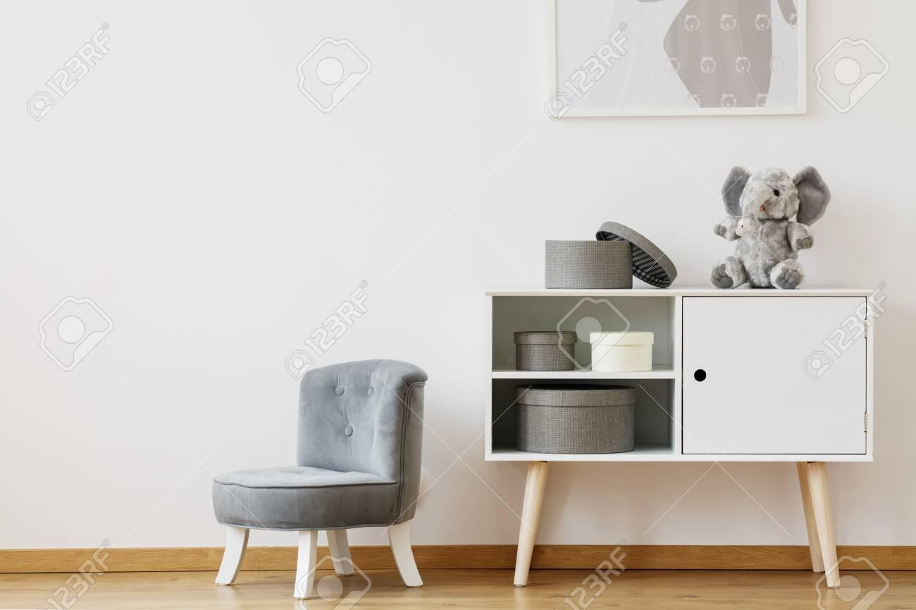 Grauer Stuhl Nahe Bei Weißem Regal Mit Kästen Und Plüschspielzeug Im