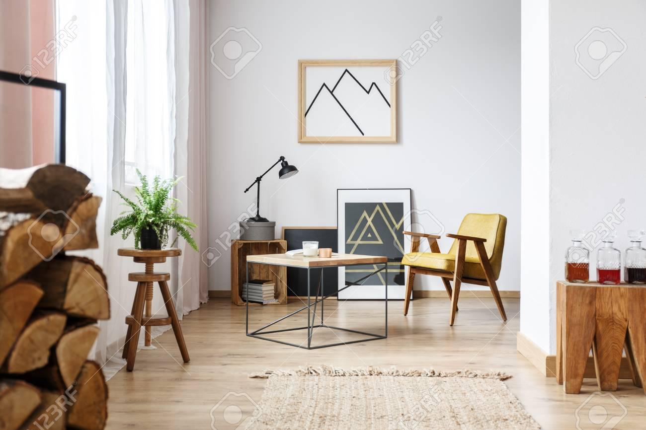 Intérieur Design Moderne D Un Salon Blanc Confortable Avec Table Basse Fauteuil Affiches Et Bois De Chauffage