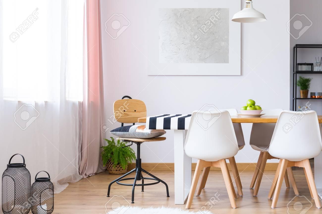 Almohada con estilo en silla clásica en la mesa de comedor con sillas  modernas blancas en la habitación con pintura de plata