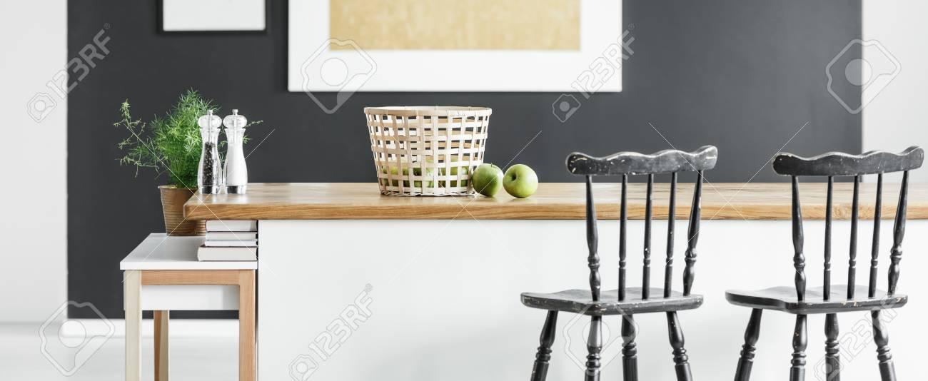 Vista panorámica de la cocina moderna minimalista con sillas de bar vintage  negro de pie en la isla de cocina blanco y madera con cesta, especias y ...