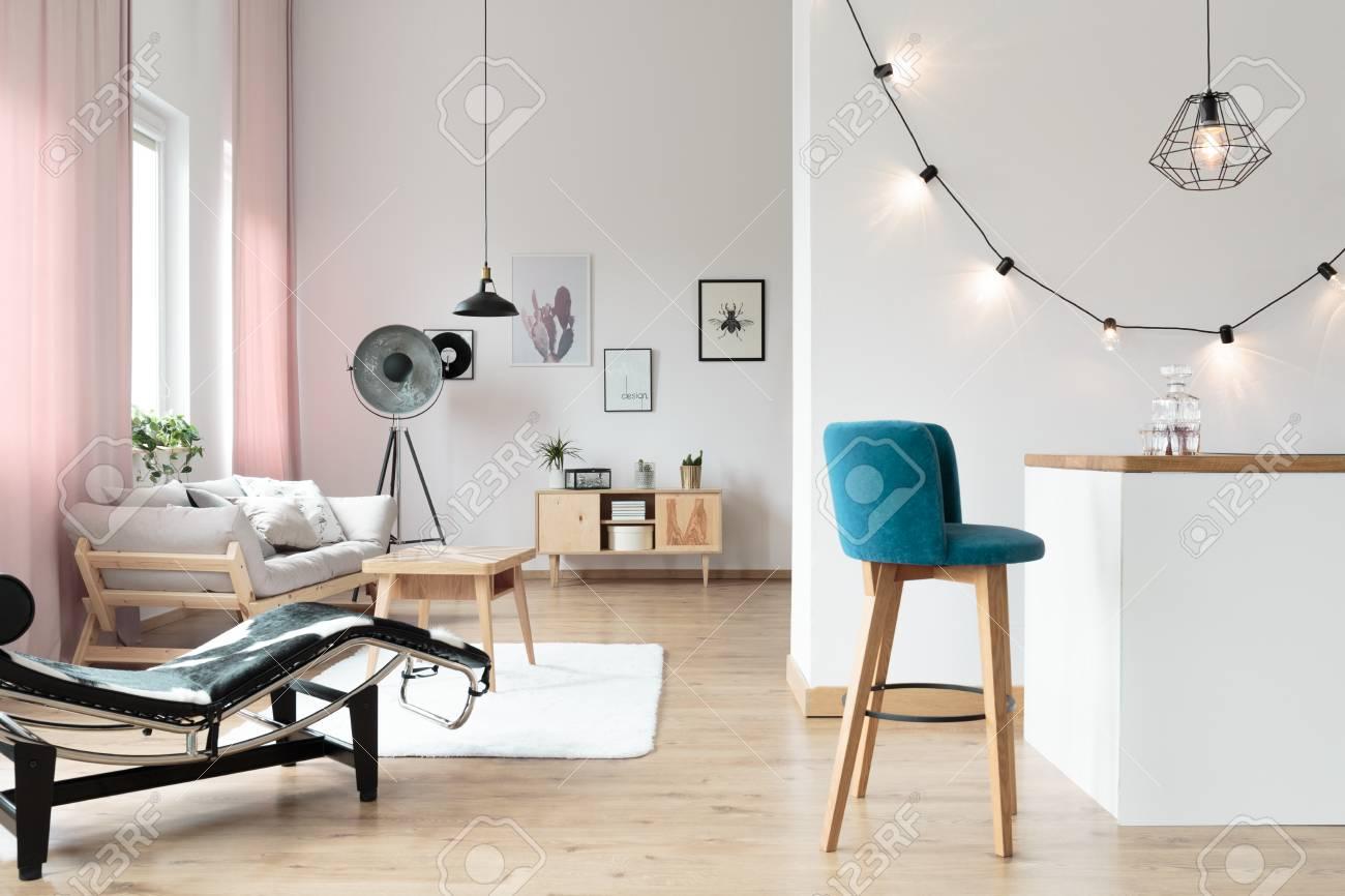 Blue barstool at white minibar in living room with lightbulbs..