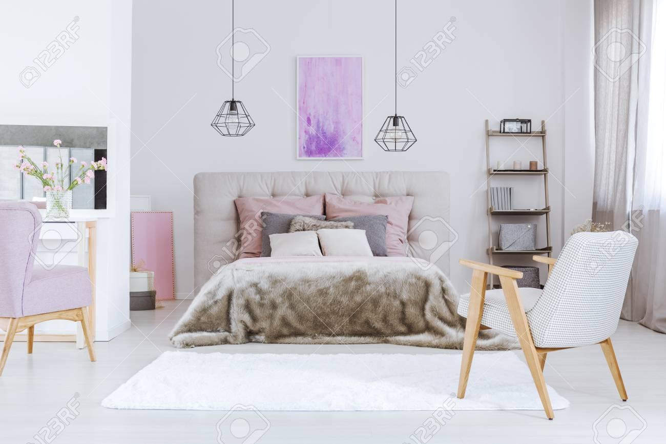 two black industrial lamps in soft feminine bedroom interior stock