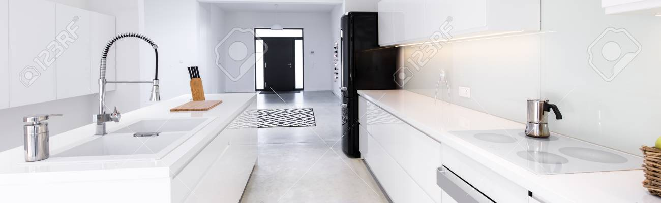 Panorama Of High Gloss White Kitchen With White Table Tops In Modern Villa  Stock Photo