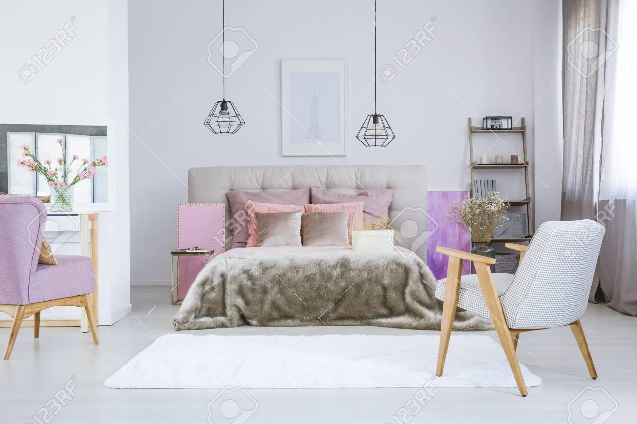 Poster An Weißer Wand über Grauem Bett Mit Rosa Accessoires Und Felldecke  Im Geräumigen Schlafzimmer Standard