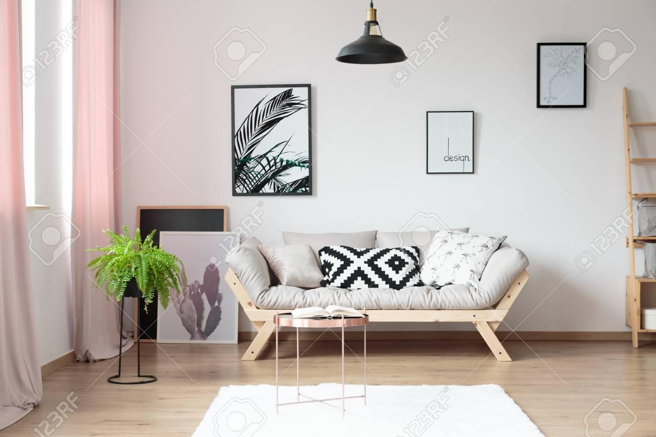 Oreillers sur canapé beige contre le mur avec des affiches dans le salon  simple avec table de cuivre et fougère