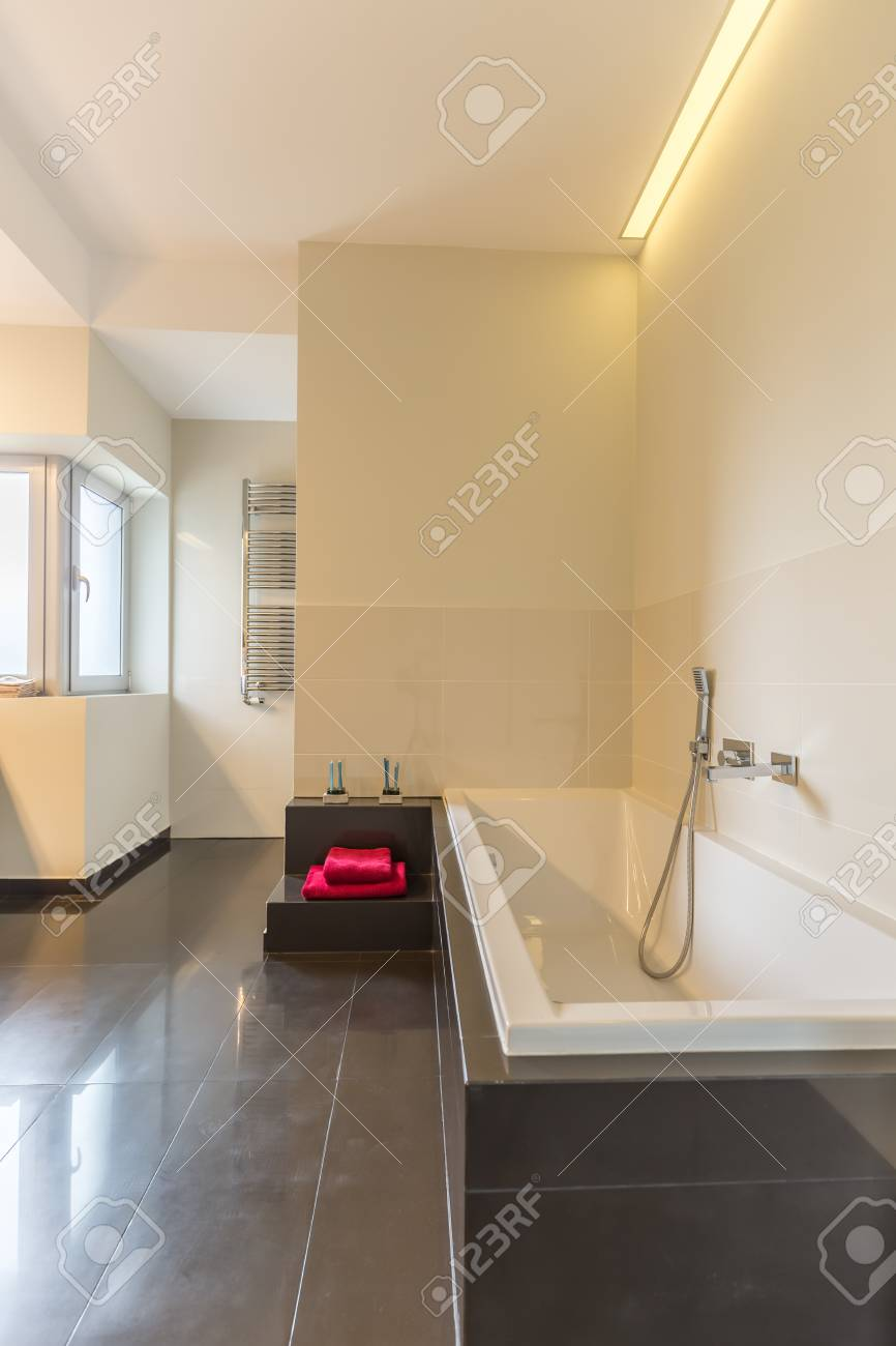 Grande salle de bain moderne conçue avec des carreaux blancs et gris