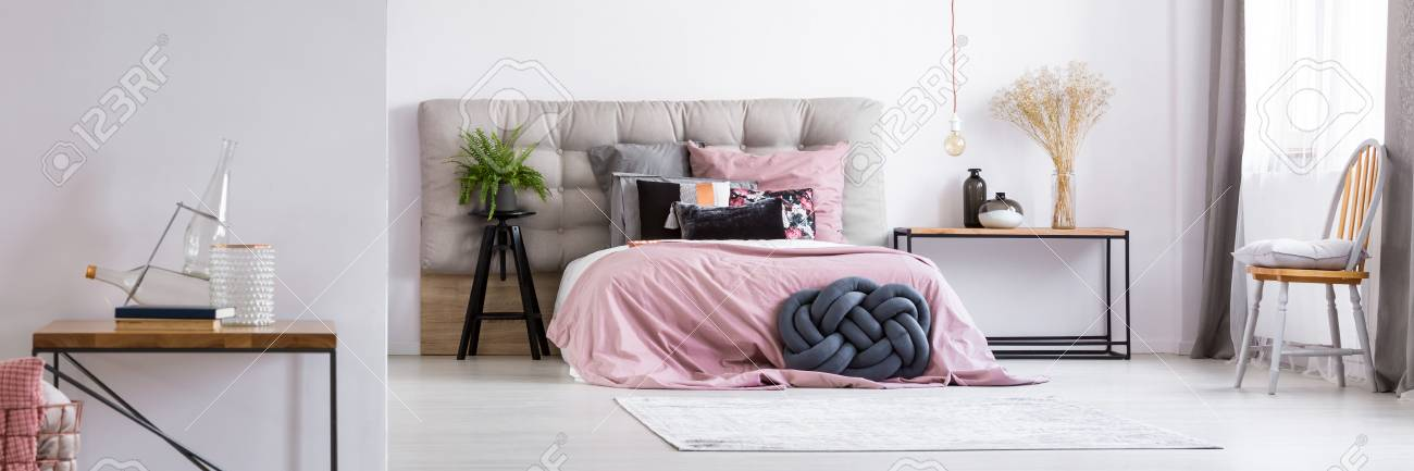 Good Spacious, Grey Minimalist Bedroom With A Lightbulb Hanging Over A  White,square Carpet Lying