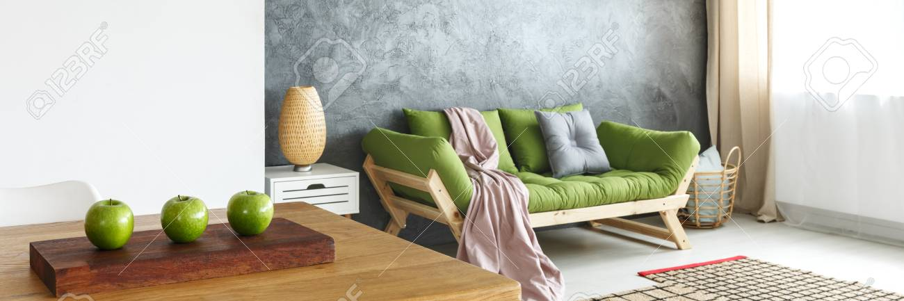 Pink Blanket And Grey Pillow On Green Sofa Against Concrete Wall In Natural  Living Room With