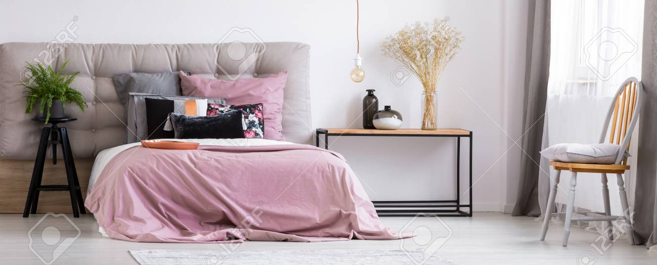 Charming, Pastel Pink Bedsheets In A Monochromatic, Grey Bedroom With A Bed  Standing Next