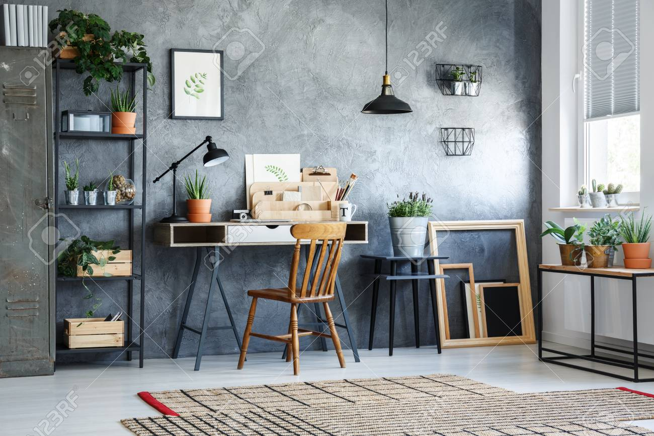 white desk home office. Classic Chair At White Desk Against Concrete Wall In Home Office With Plants Stock Photo -