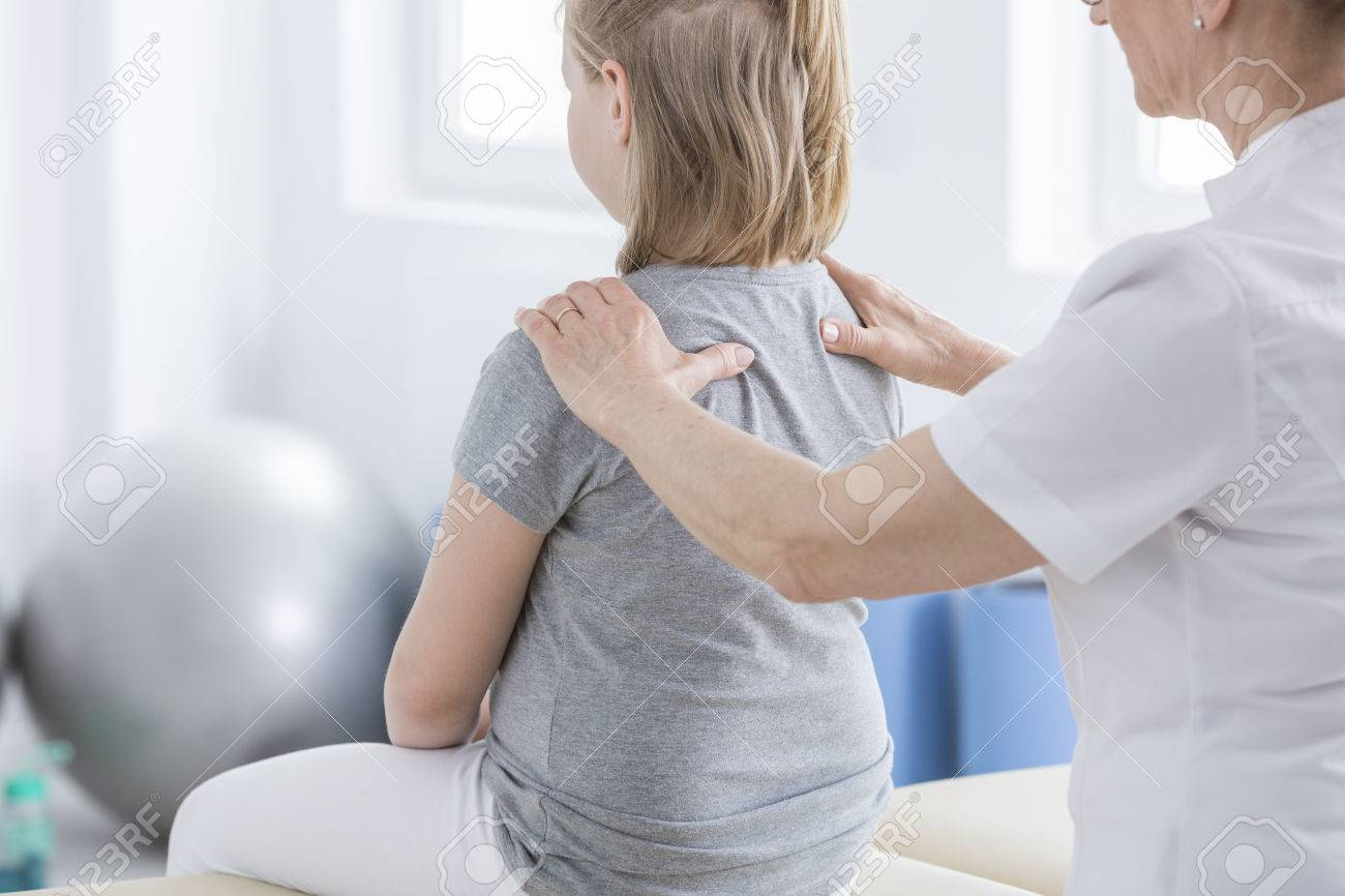 Physiotherapist massaging a girl with spine deformity during session in rehabilitation room - 87171314