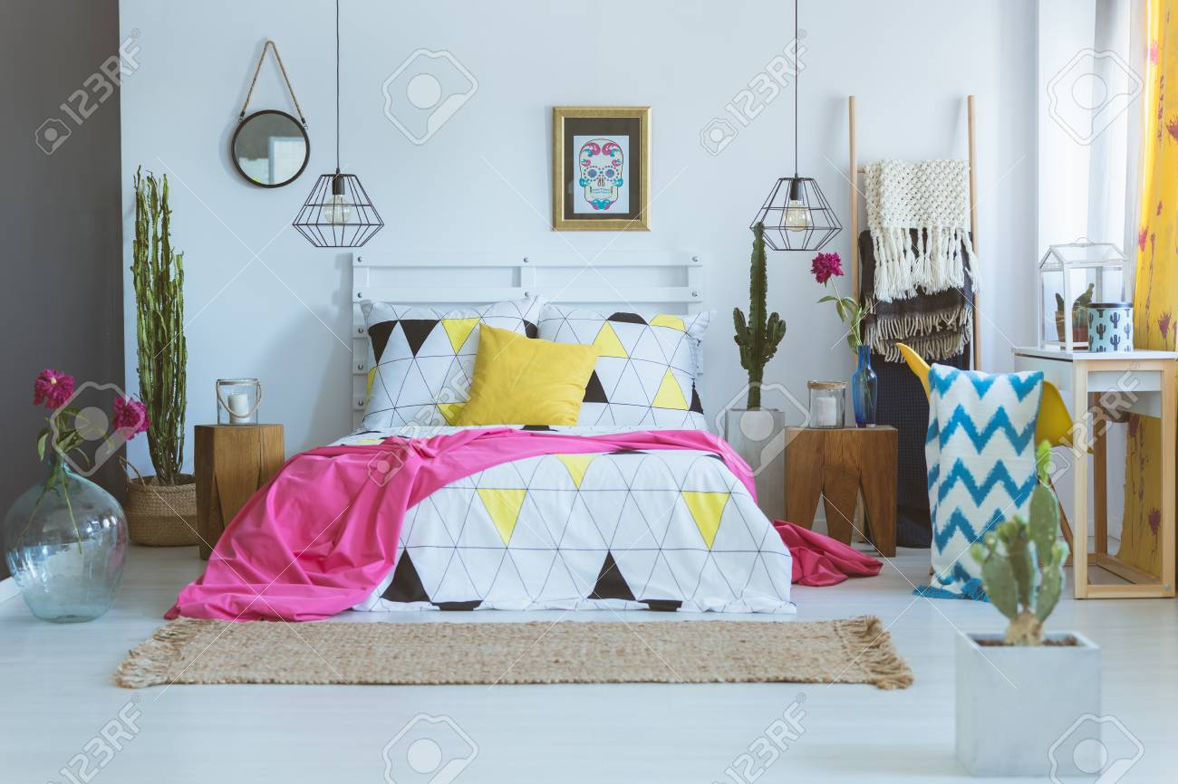 Coverlet with geometric pattern on king-size bed in unique bedroom...