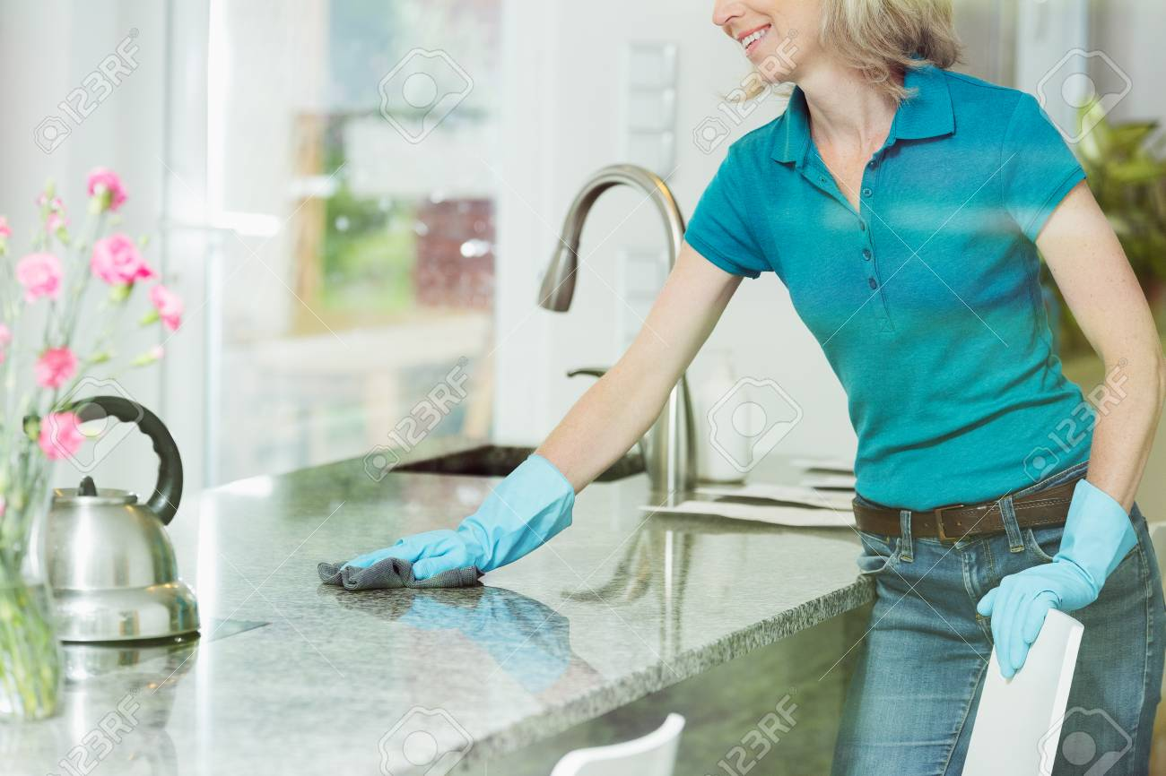 professional house cleaning service concept smiling woman wiping down marble kitchen countertop using domestic cleaner