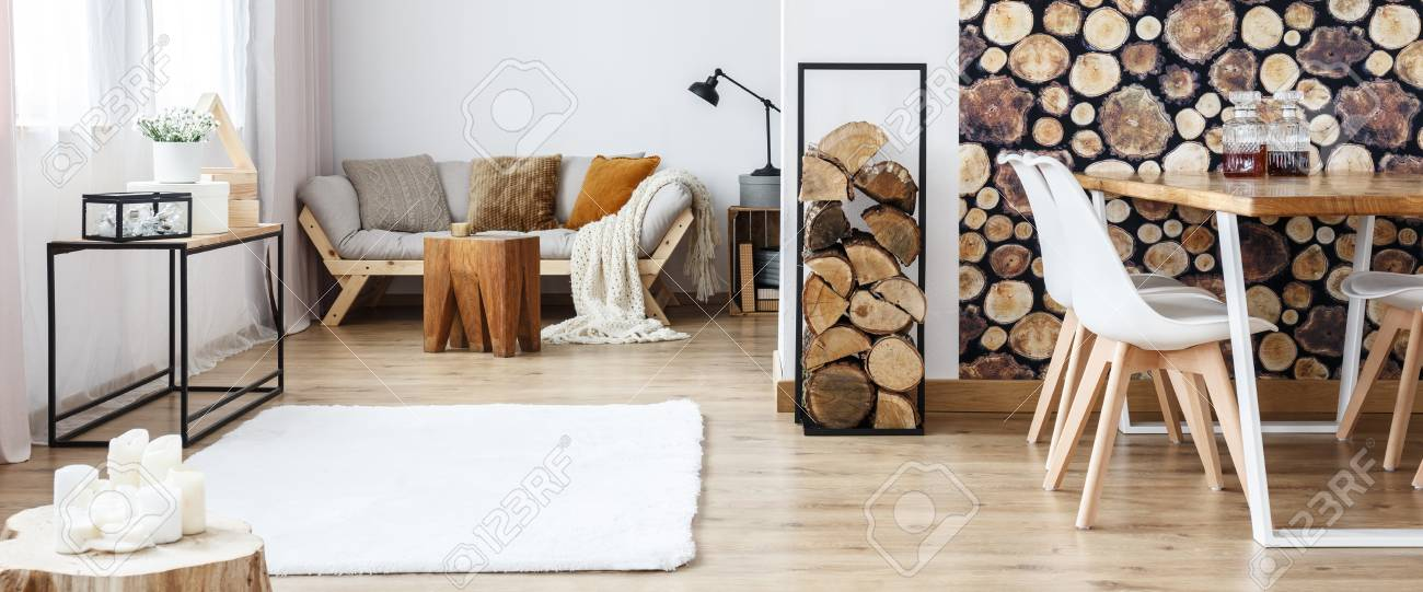 Stock Photo   Warm Multifunctional Room With Sofa And Dining Table Against  Wall With Log Wallpaper