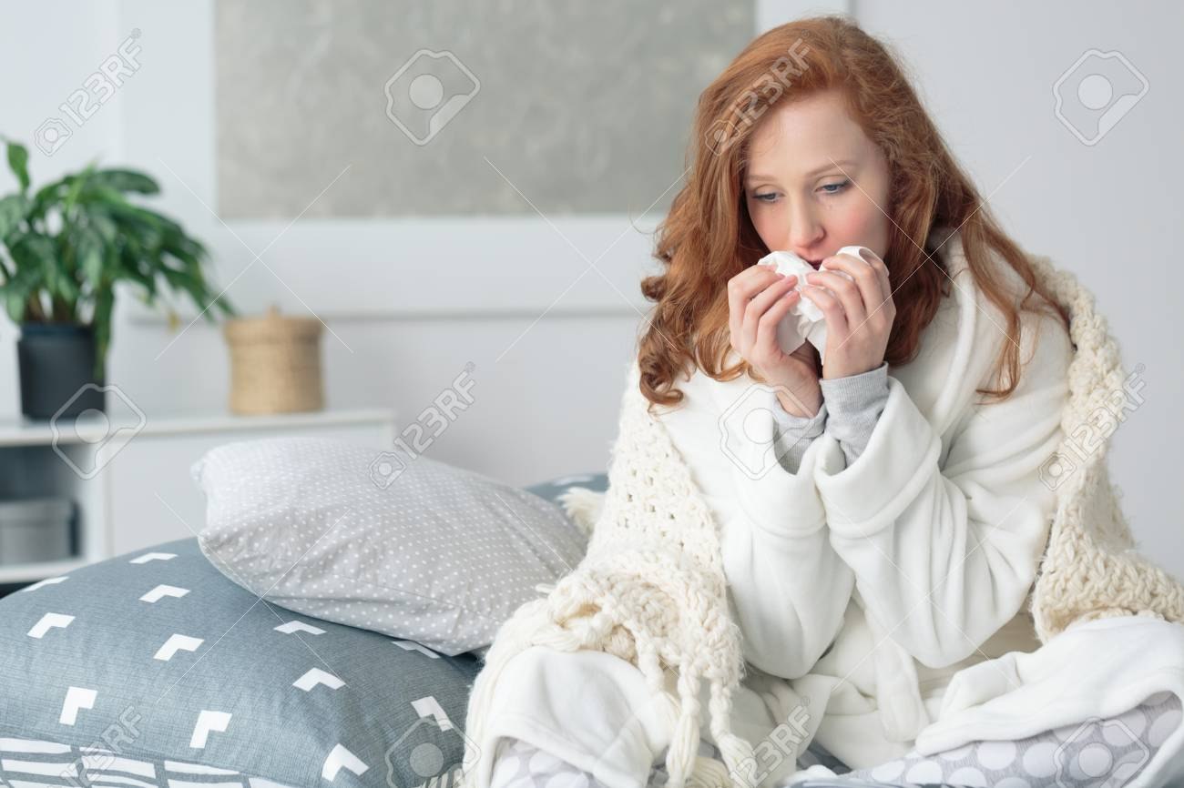 Miserable woman sitting on the bed wrapped in blanket, feeling sick with flu, having fever and blowing runny nose with handkerchief - 87211311