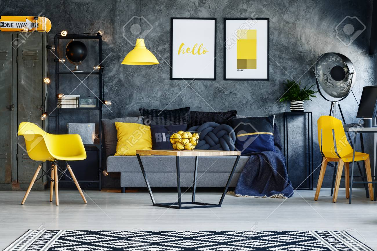 Yellow Chairs In Dark Living Room With Poster On Concrete Wall