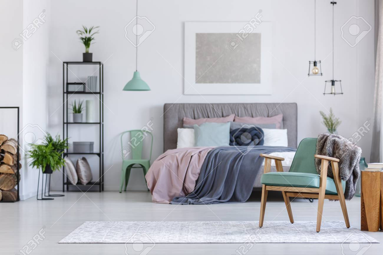 Mint chair next to king-size bed with pink and grey bedsheets..