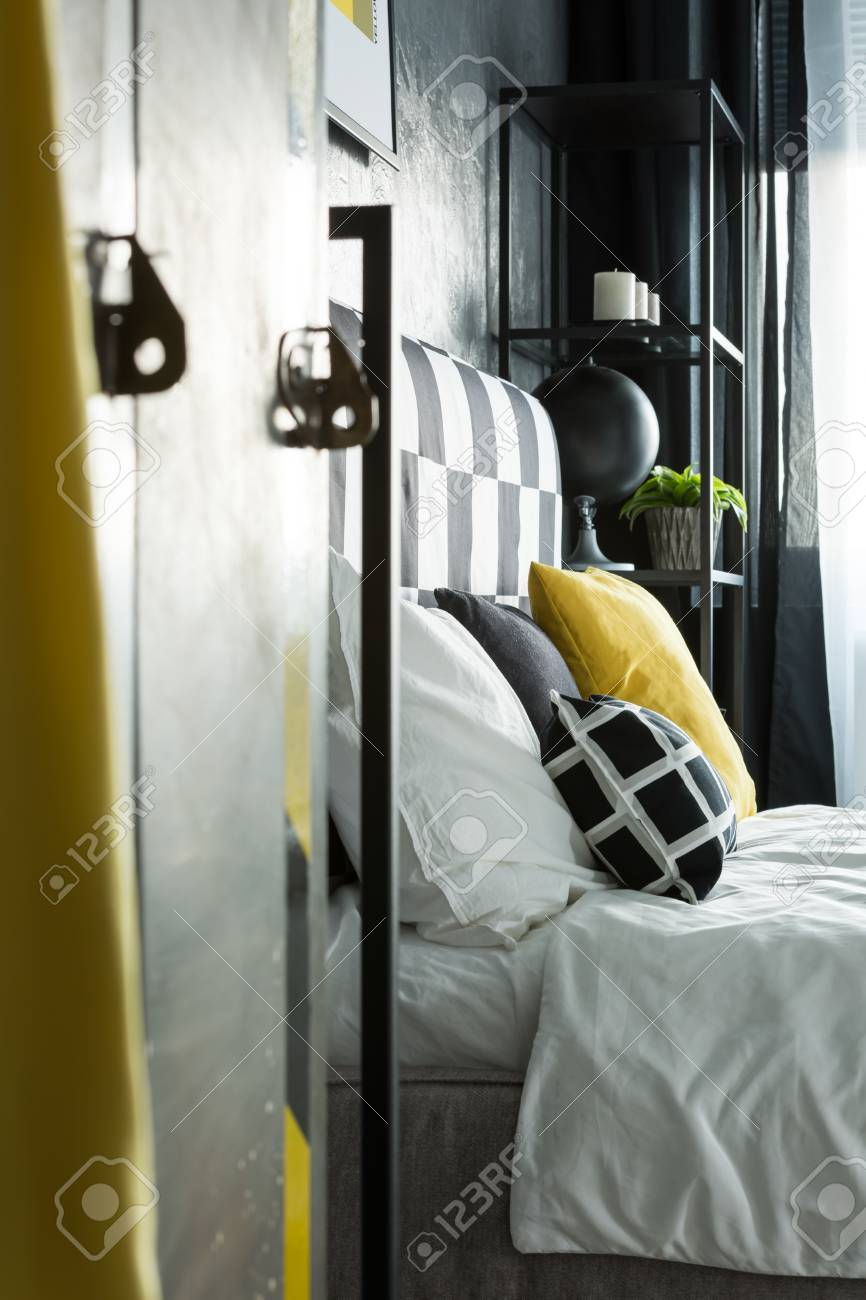 Side angle of metal shelf in bedroom with black, white and yellow..