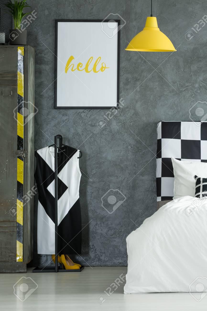 Robe à la mode noir et blanc sur cintre dans la chambre avec lampe jaune et  simple affiche sur le mur