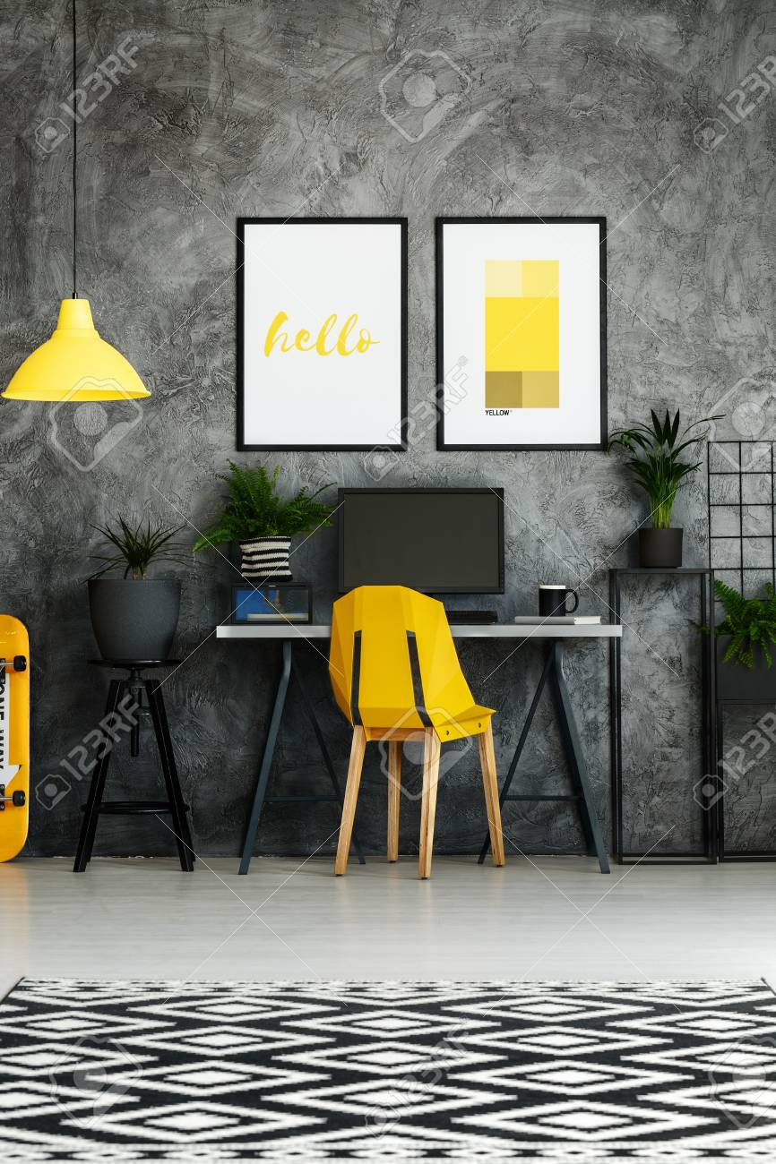 Black and white carpet in contemporary work zone with yellow chair and posters on concrete wall