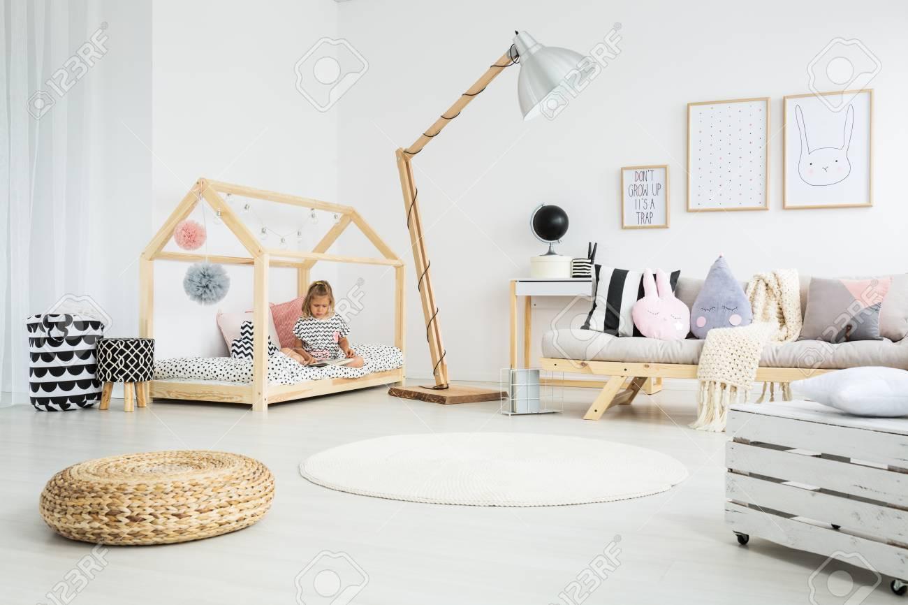 . Girl sitting on handmade bed in cute scandinavian style kid room