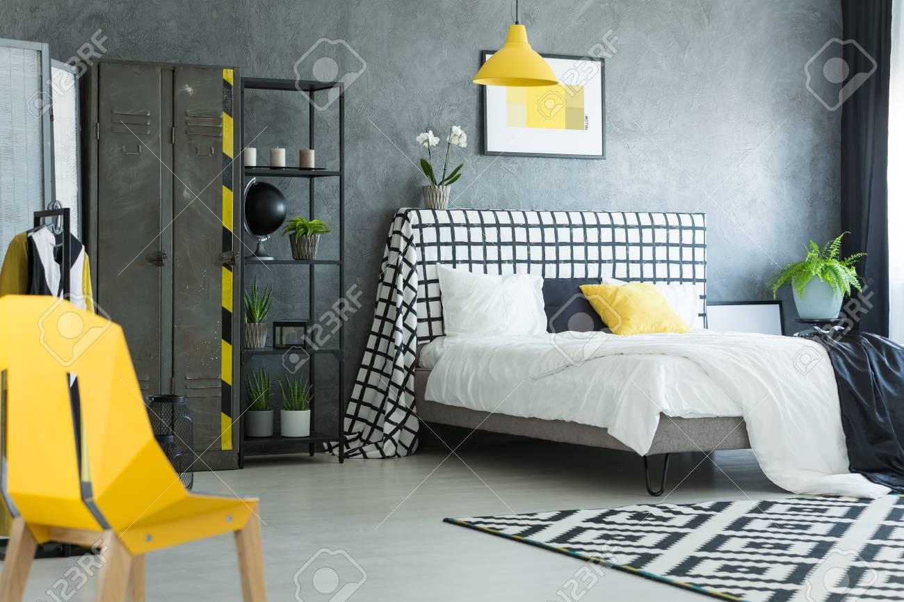 Chaise de designer jaune dans une chambre noire et blanche avec tapis  géométrique et étagère métallique