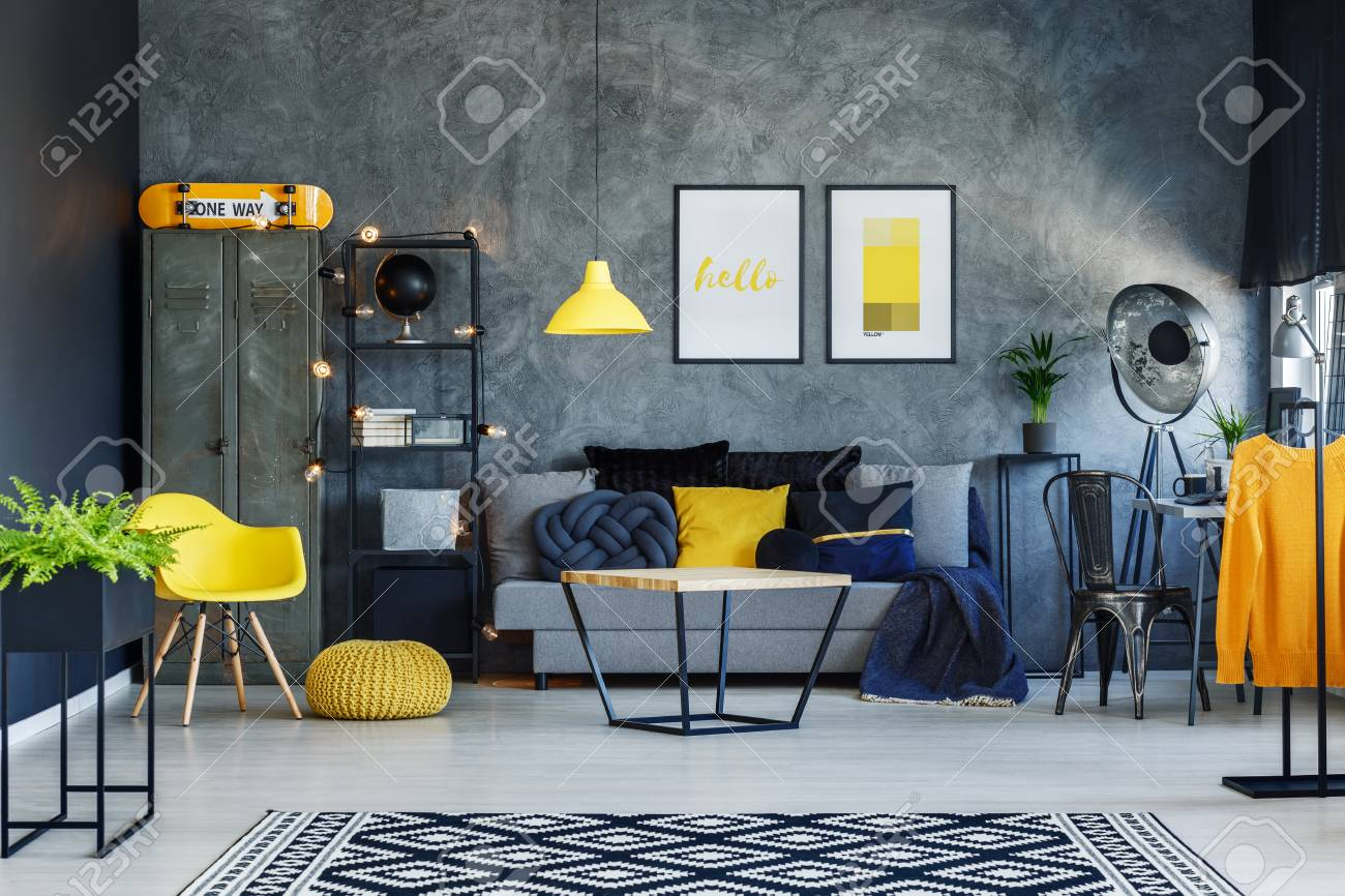 Orange Sweater On Hanger In Scandinavian Style Living Room With Grey Sofa  And Yellow Chair Stock