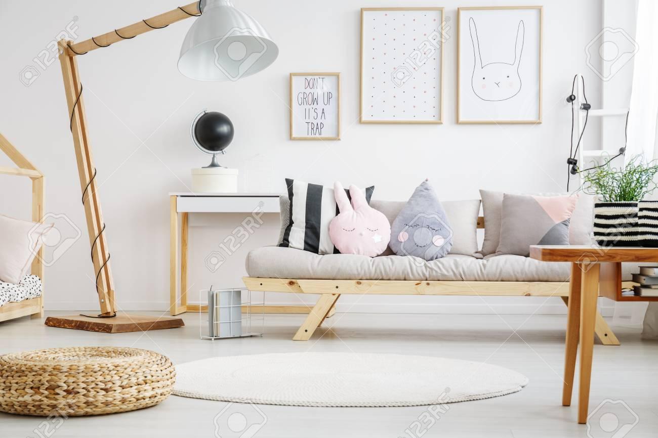 Designed Lampe In Der Nähe Von Beige Sofa Mit Kissen Im Kinderzimmer Mit  Plakaten Auf Weiße