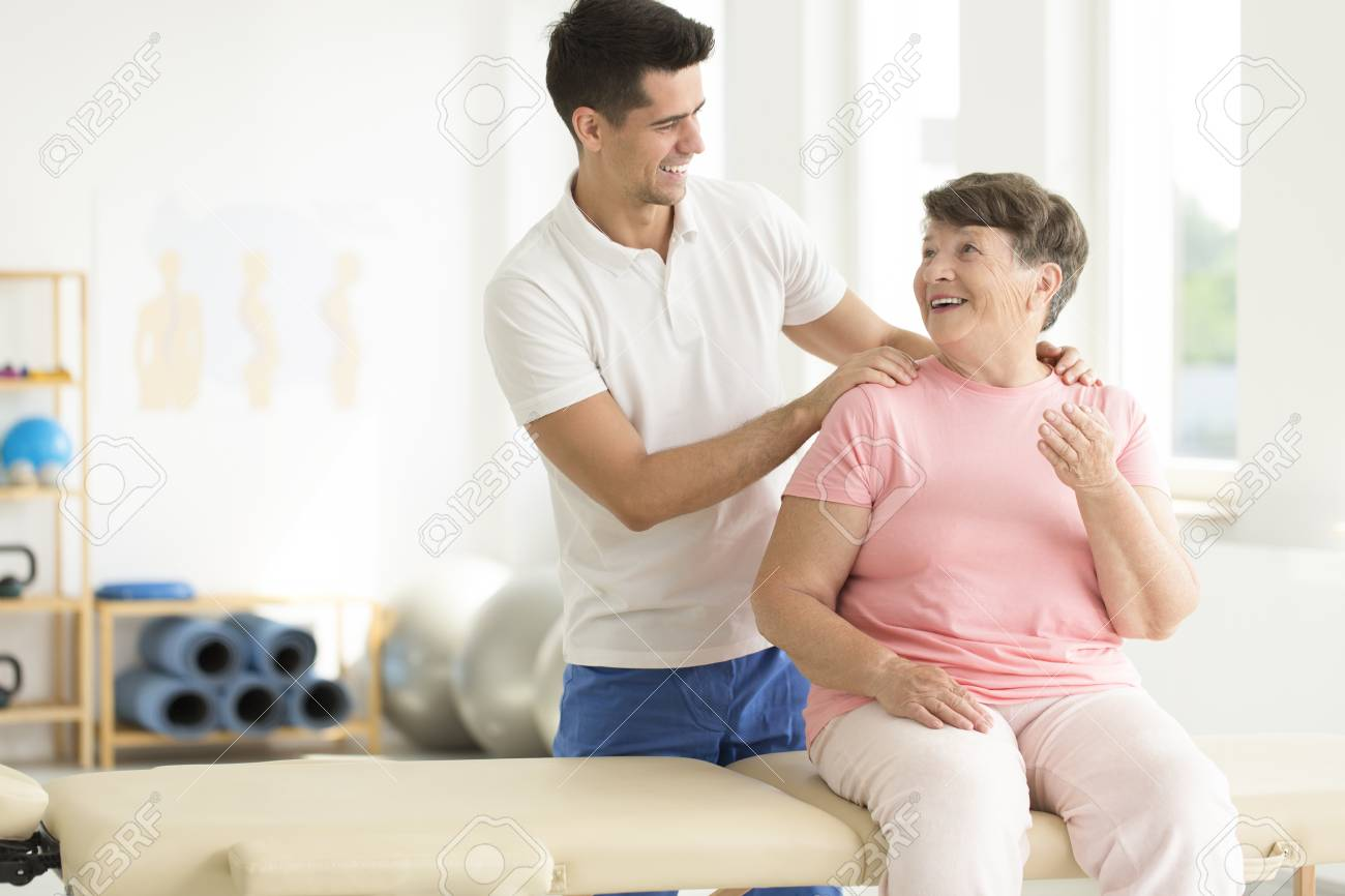 Physiotherapist performing a rehabilitation session with his senior ward - 87560706