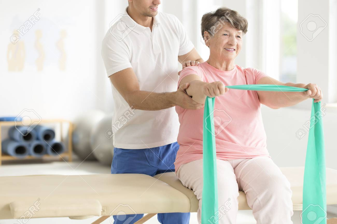 Elderly woman doing active pnf exercises with a teal scarf as a part of her rehabilitation program with a physiotherapist - 87560710