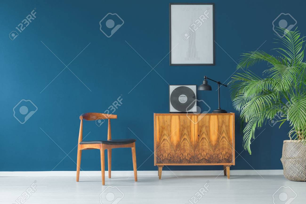 Stylish apartment interior with blue wall decorated in vintage style with wooden cupboard,chair, mock-up poster and tropical potted plant - 87560777