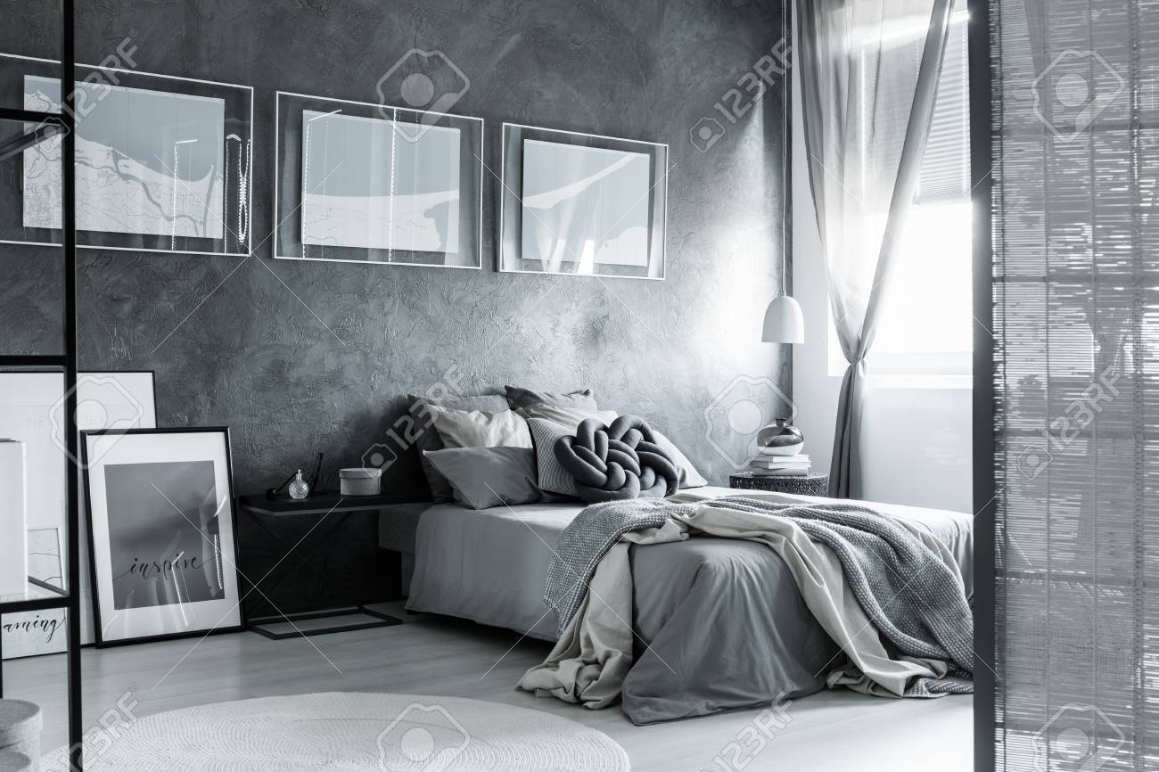Screen and posters in dark grey bedroom with bedsheets on king-size..