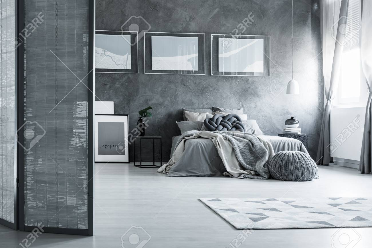 Contrast posters on textured wall in grey bedroom with screen..