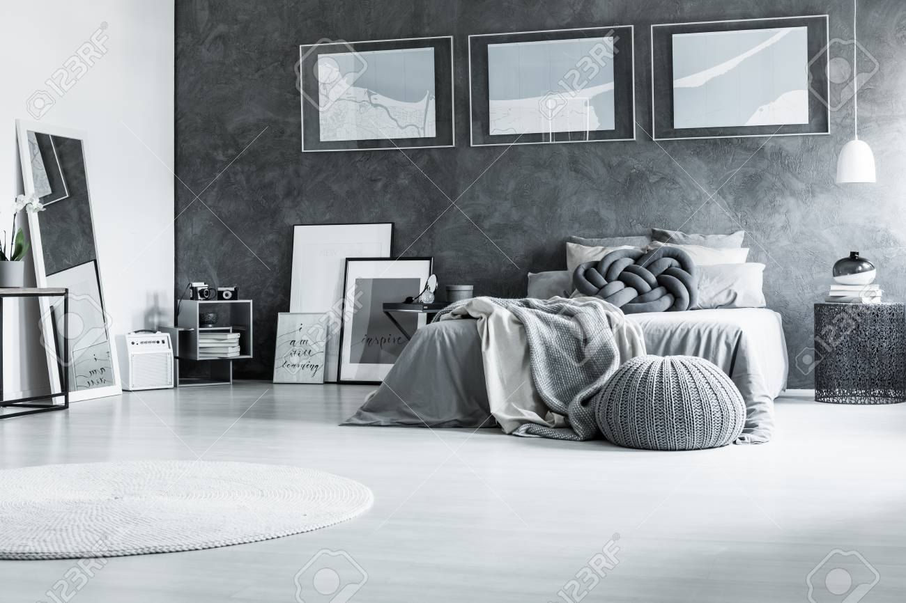 White carpet and pouf in restful black and white bedroom with..