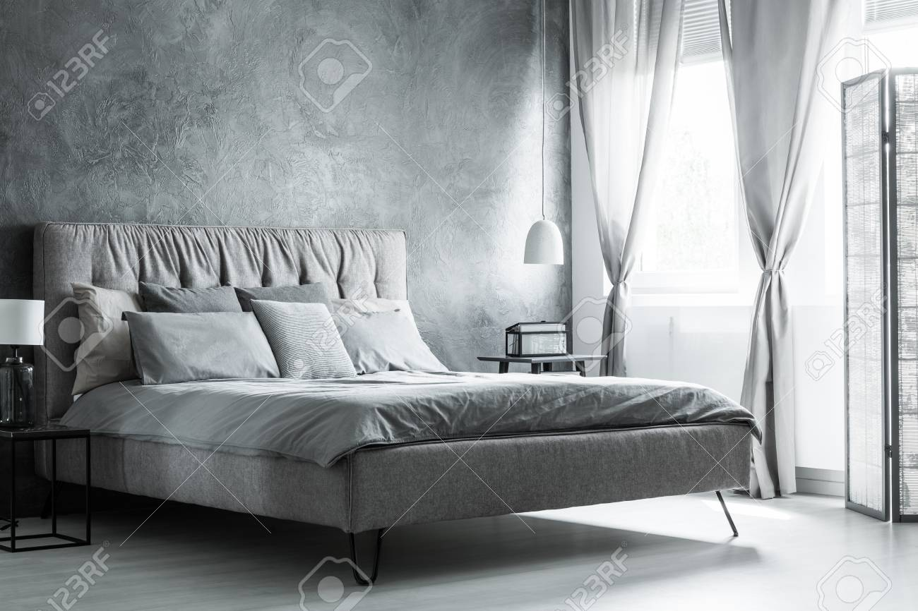 Grey Pillows On King Size Bed And Glass Lamp On Black Nightstand