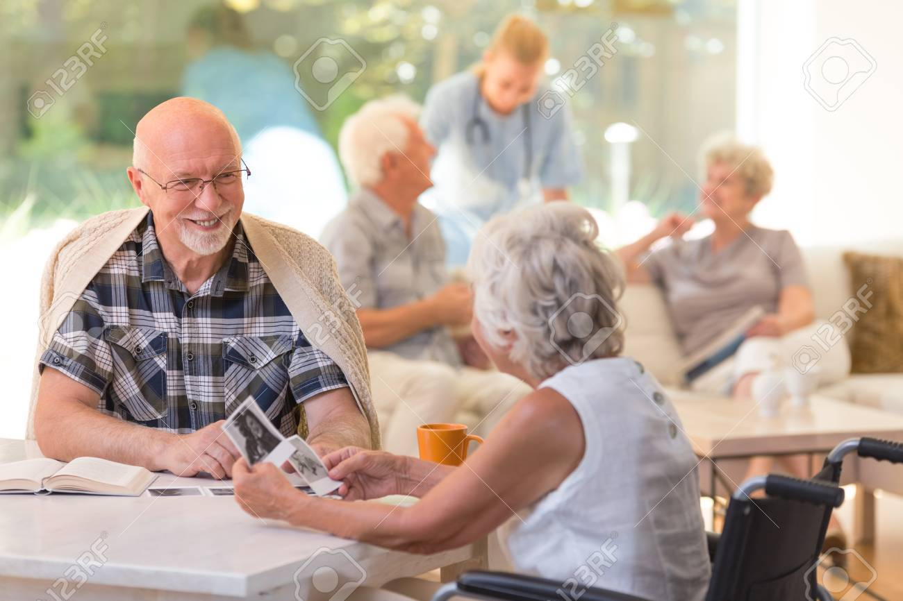 Married couple of elders sitting together and watching old photos at the nursing home - 89250364