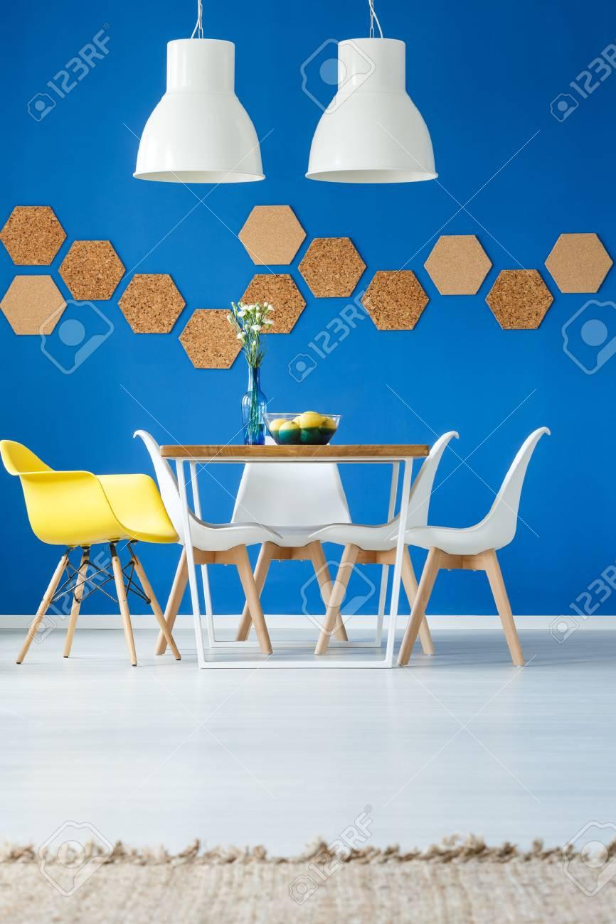 Lámparas blancas sobre la mesa con la silla amarilla en el comedor con  elemento de diseño ecológico en la pared azul