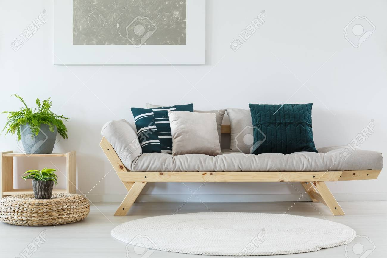 Plant On Pouf Near Beige Settee With Pillows In Living Room With ...