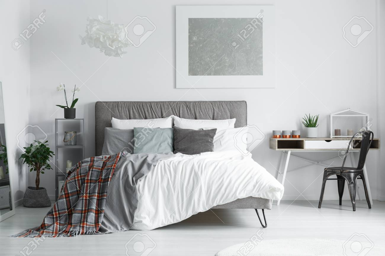 Red And Grey, Checkered Bedsheets Lying On A King Size Bed In A Minimalist