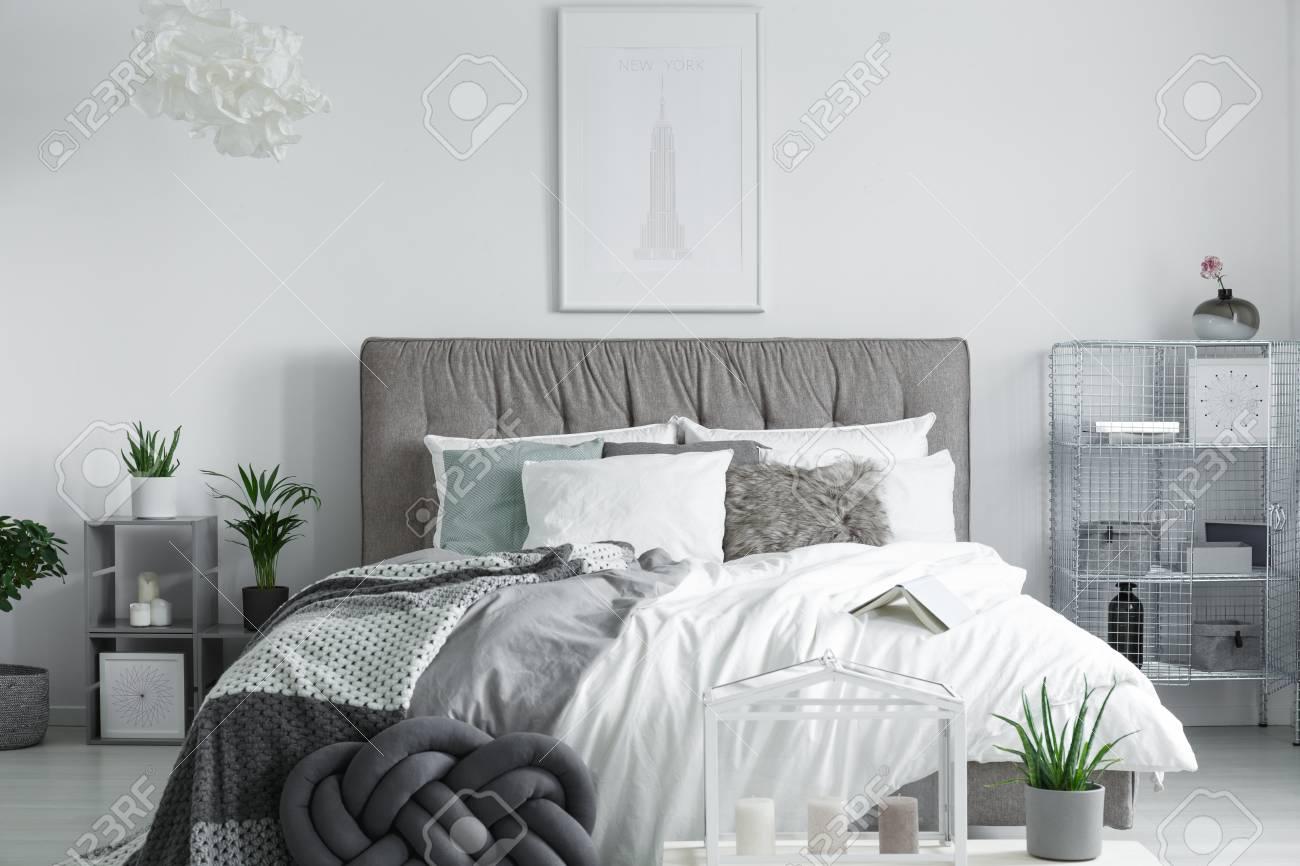 Livre ouvert couché sur les draps d\'un lit king-size, gris, dans un  intérieur spacieux chambre à coucher