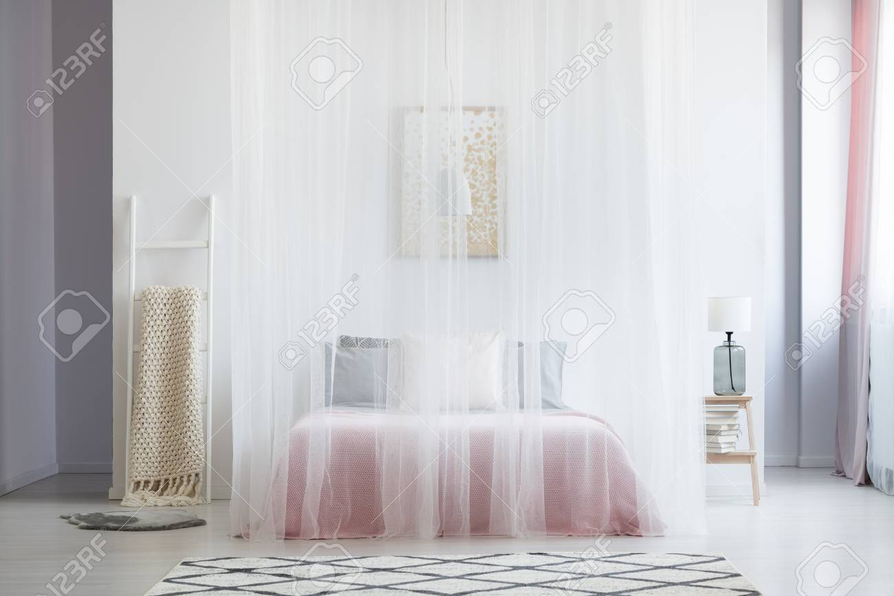Patterned carpet in bedroom with king size bed covered by veil and beige blanket on