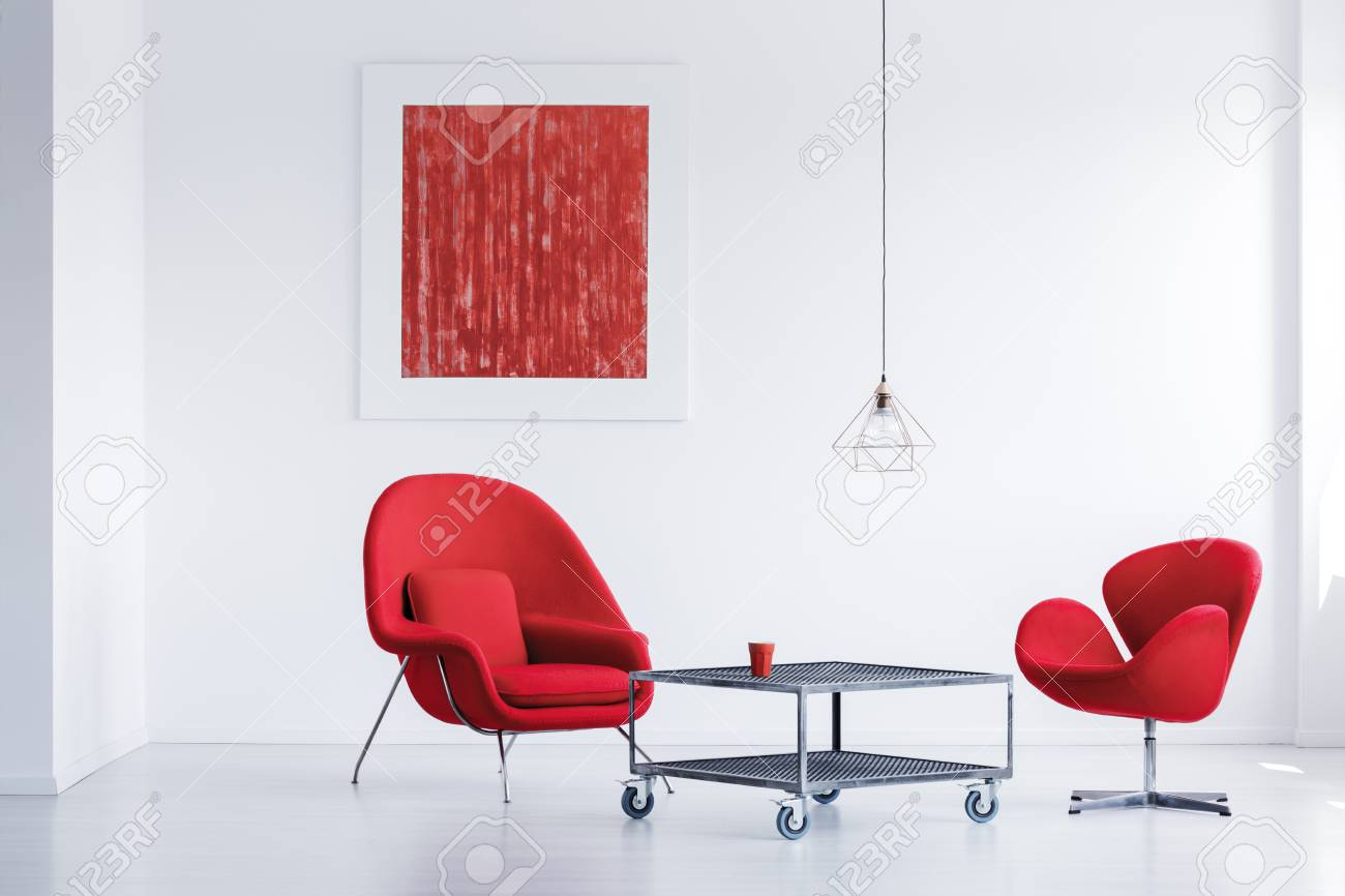 White simple waiting room with two red chairs by the industrial..